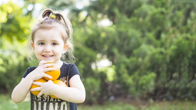 smiling-girl-holding-fresh-oranges-park 23-2147893029